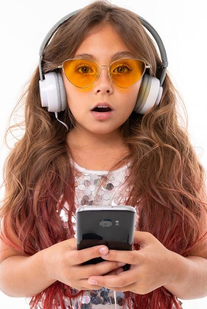 Удивленная девушка в желтых очках, с большими наушниками держит черный смартфон Premium Фотографии