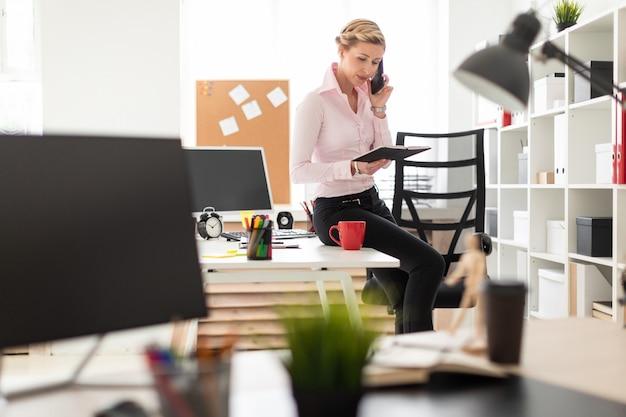若いブロンドの女の子がオフィスの机の上にしゃがみ、電話で話し、ノートを手に持っていました。 Premium写真