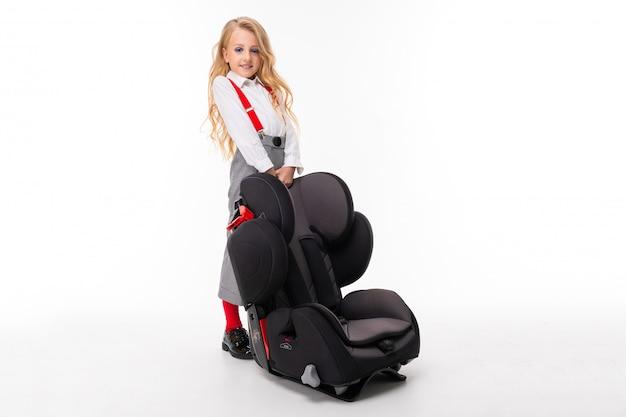 化粧と白いシャツ、赤いプルアップ、檻の中のパンツ、赤い靴下、赤ちゃんの椅子と靴でブロンドの髪を持つ少女。 Premium写真