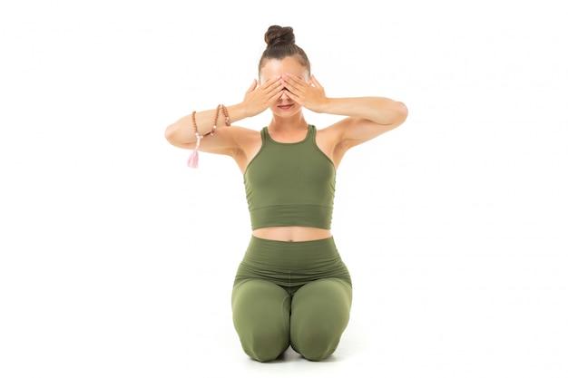 Молодая кавказская гимнастка с атлетическим телом сидит на полу с закрытыми глазами, занимаясь йогой и медитацией Premium Фотографии