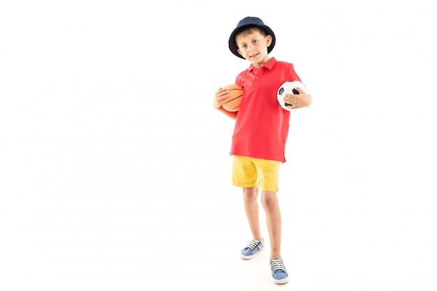 Маленький мальчик в панаме, желтой майке, красных шортах и белых кроссовках стоит с баскетбольными и футбольными мячами Premium Фотографии