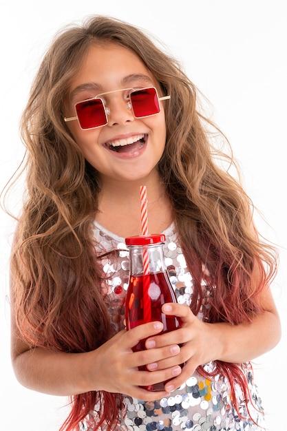 ヒントピンクで染められた長いブロンドの髪を持つ十代の少女、光沢のある明るいドレス、黒と白のスニーカー、メガネ、ヘッドフォンで立って、ストライプのチューブが付いたガラス瓶にジュースを手で押し Premium写真