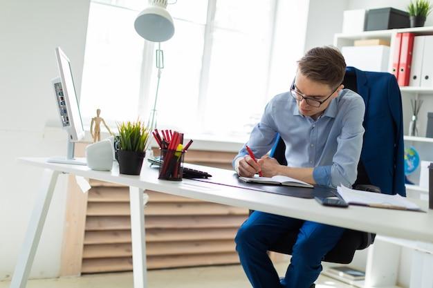 若い男がオフィスのコンピューターの机に座って、ノートに書いています。 Premium写真