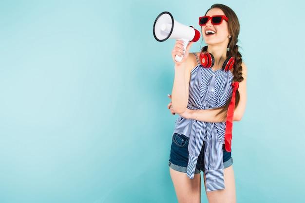 Молодая сексуальная женщина с наушниками и громкоговорителем Premium Фотографии