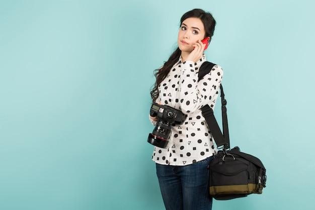 カメラとそのケースを持つ若い女 Premium写真