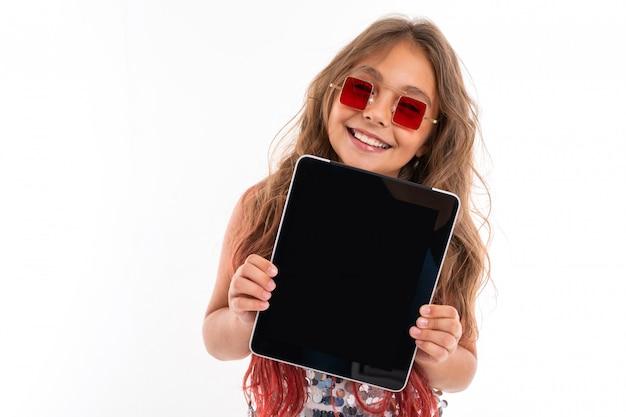 かなり白人少女は大きなタブレット、白い壁に分離された画像を示しています Premium写真