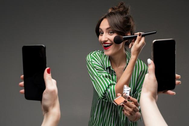 幸せな白人女は鏡の前でブラシで化粧をし、灰色の壁に分離された写真を撮る Premium写真