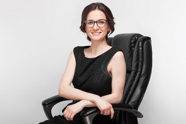 肘掛け椅子に座っている黒のドレスで美しい女性の写真 Premium写真