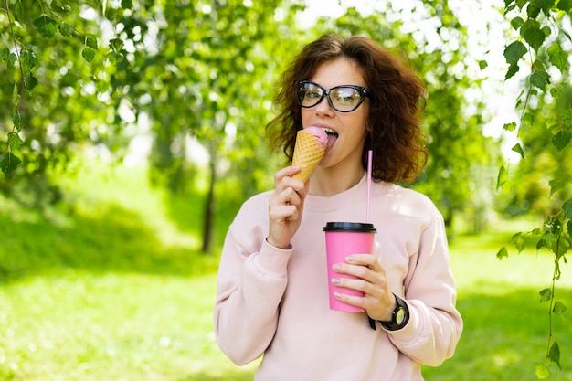 かなり若い白人女性はコーヒーとアイスクリームのある公園で散歩に行く Premium写真