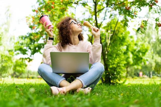 かなり若い白人女性はコーヒーとアイスクリームのカップを持つ公園でフリーランスに従事しています。 Premium写真