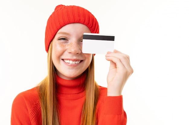 赤い髪、赤いフーディ、白い背景で隔離のカードと帽子と幸せなティーンエイジャーの女の子 Premium写真