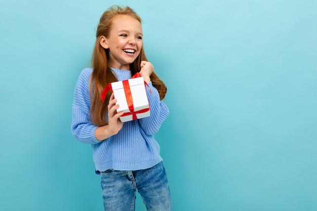 Очаровательная счастливая европейская девушка с подарком, полученным на день святого валентина на голубом фоне Premium Фотографии