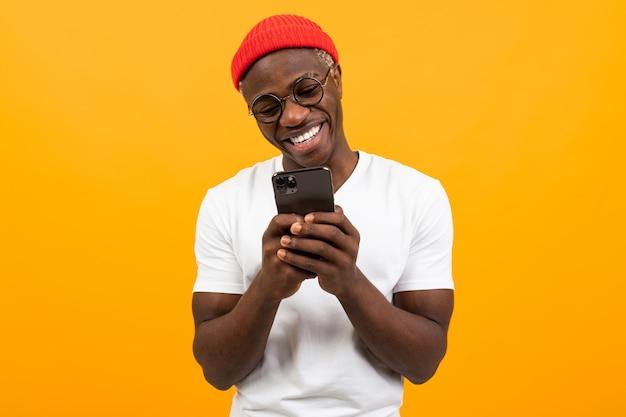 彼の手でスマートフォンを押しながら黄色の背景にメッセージを送信する笑顔のアメリカ人 Premium写真