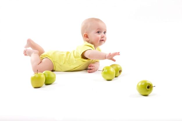 Улыбающийся ребенок лежал на земле, чтобы включить яблоки Premium Фотографии