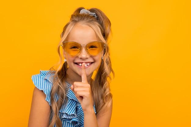 Очаровательная белокурая девушка в платье и солнечных очках просит потише, держит палец в рот на желтом фоне Premium Фотографии