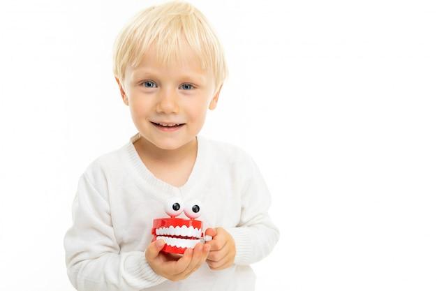 Крупный белокурый ребенок мужского пола с игрушкой в виде белой зубной челюсти на белом фоне Premium Фотографии