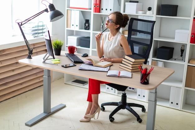 若い女の子がコンピューターの机に座って、開いた本と鉛筆を手に持っています。 Premium写真
