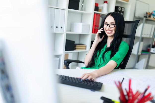オフィスで眼鏡をかけた若い女の子の笑顔は電話で話し、キーボードに手を握っています。 Premium写真