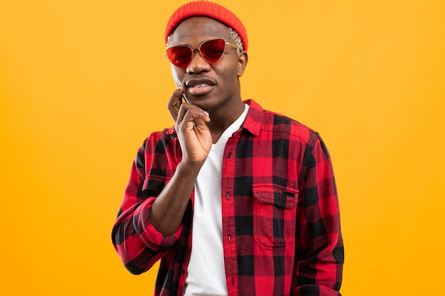 コピースペースとオレンジ色の赤いレトロなメガネでスタイリッシュな深刻な黒アフリカ人 Premium写真