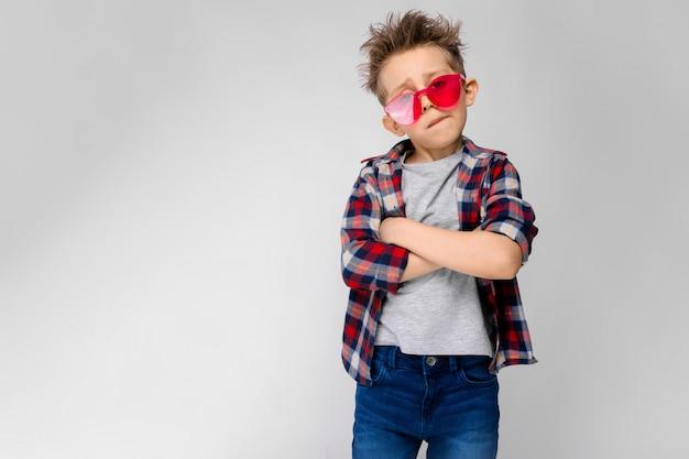 格子縞のシャツ、グレーのシャツ、ジーンズのハンサムな男の子が立っています。赤いサングラスの少年。少年は腕を胸にかざした。 Premium写真