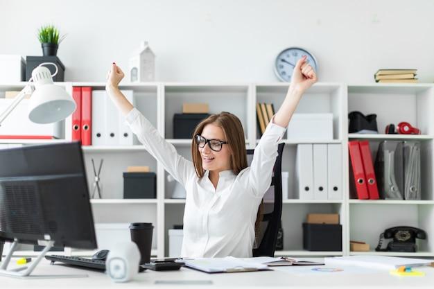 オフィスのコンピューターデスクに座って手を挙げた少女。 Premium写真
