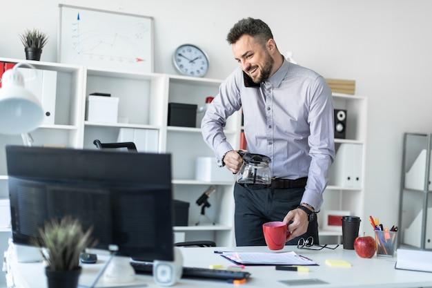 オフィスの若い男がテーブルの近くに立って、肩で電話を持ち、モニターを見て、カップにコーヒーを注いでいます。 Premium写真