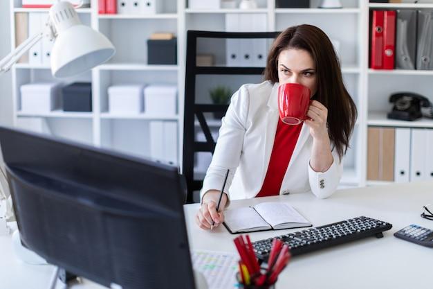 コンピューターデスクのオフィスに座って、赤いカップを保持している若い女の子。 Premium写真