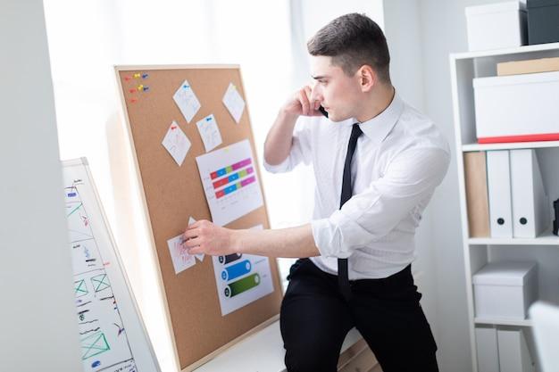 ステッカーとボードの近くに立って、電話で話しているオフィスの若い男。 Premium写真