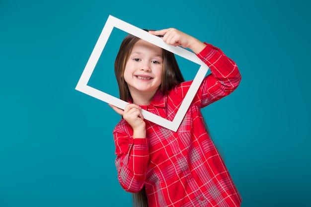 黒髪の市松模様のシャツのかわいい女の子は、額縁を保持します。 Premium写真