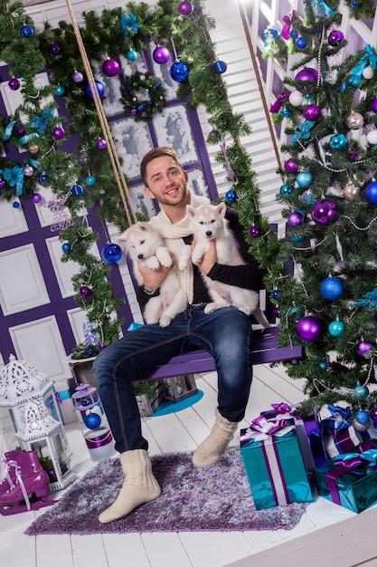 クリスマスの装飾の横にあるテラスに座っている美しい男 Premium写真