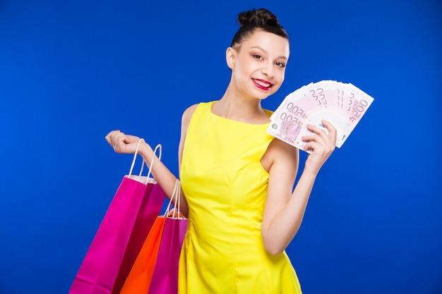 ショッピングとお金を持つ少女 Premium写真