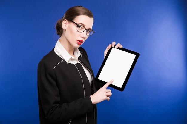 手でタブレットを持つ少女のクローズアップの肖像画 Premium写真