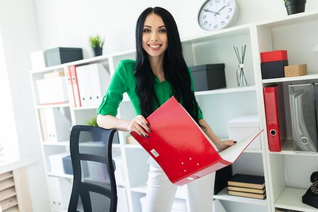オフィスの若い女の子がドキュメントのフォルダーを保持しています。 Premium写真