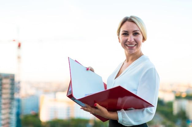 若い魅力的なビジネス女性の手で紙フォルダーと屋根の上に立つ Premium写真