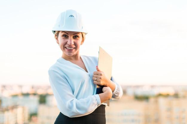 ヘルメットでかなり若い職長が手でタブレットで屋根の上に立つ Premium写真