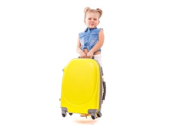 青いシャツ、白いショートパンツ、サングラスの魅力的なかわいい女の子が黄色のスーツケースの近くに立つ Premium写真