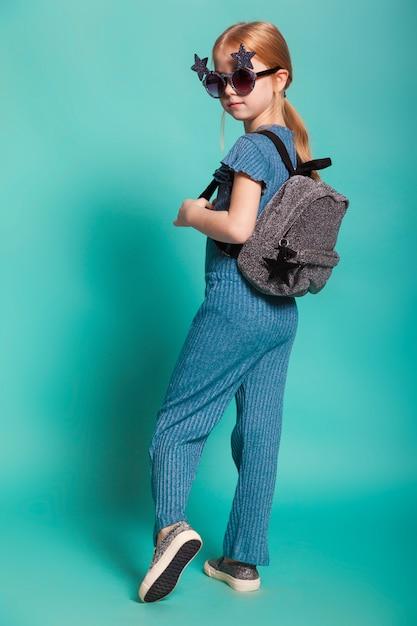 スタイリッシュな服とサングラスの尾を持つ少女 Premium写真
