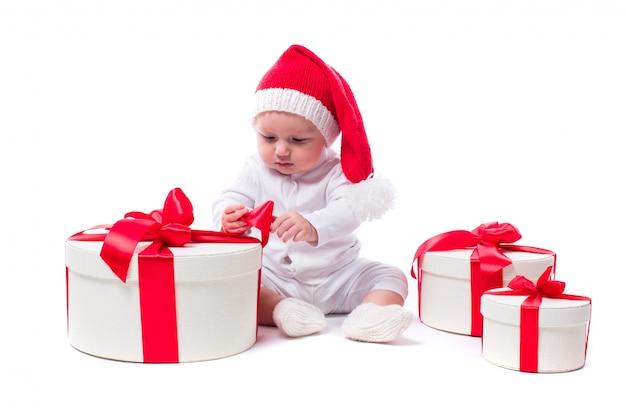 新年の帽子と白い体に座っている美しい子供 Premium写真