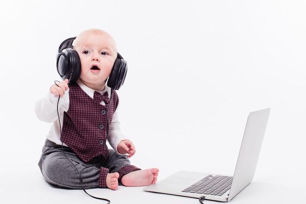 ヘッドフォンを着てラップトップの前に座っているかわいい赤ちゃん Premium写真