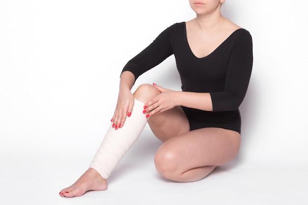 女の子は彼女の足の弾性包帯を修正します Premium写真