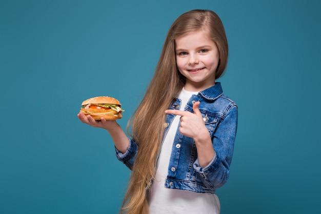 長い茶色の髪とジーンズのジャケットの小さなかわいい女の子はハンバーガーを保持します。 Premium写真