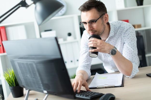 メガネの若い男がオフィスのテーブルのそばに立ち、一杯のコーヒーを手に持ち、コンピューターで動作します Premium写真