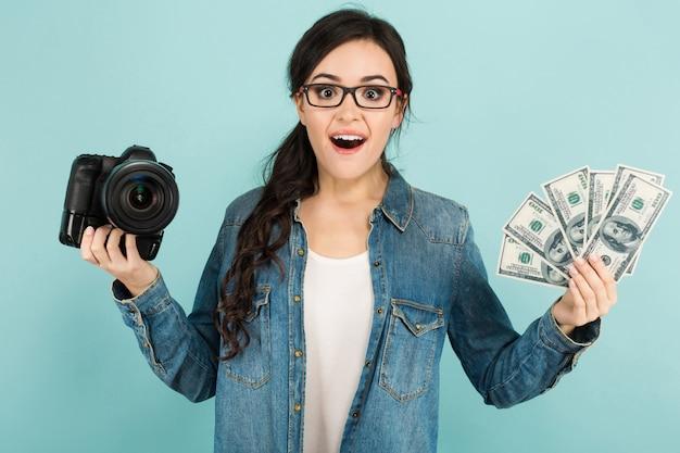 カメラと現金を持つ若い驚く女性 Premium写真