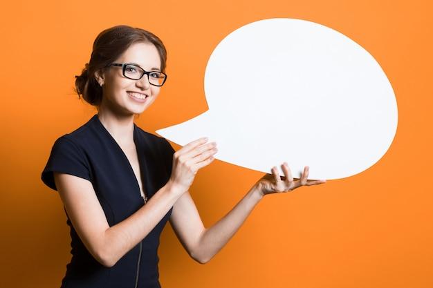 Портрет уверенно красивой молодой бизнес-леди с пузырем речи в ее руках стоя на оранжевой стене Premium Фотографии