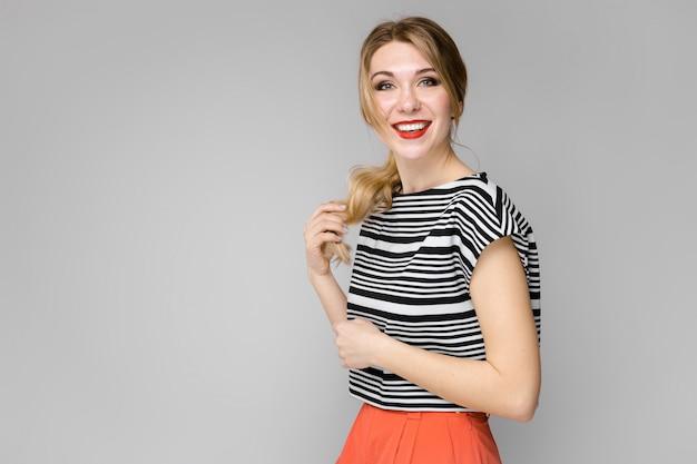 灰色の壁に立っている彼女の髪を持って笑顔ストライプブラウスで魅力的な若いブロンドの女の子 Premium写真