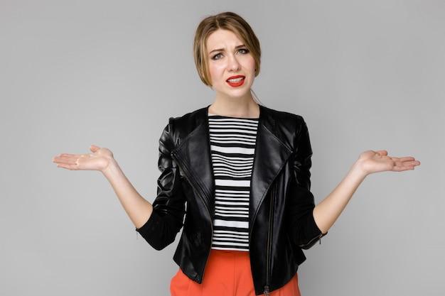 灰色の壁に立っているストライプブラウスと革のジャケットで魅力的な若い困惑したブロンドの女の子 Premium写真