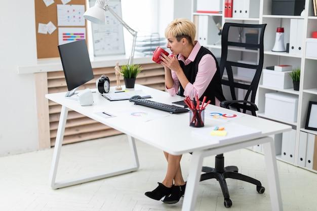 女の子はコンピューターのオフィスで働いており、カップを持っています。 Premium写真