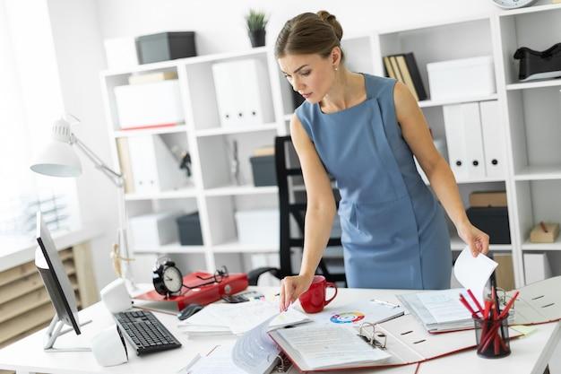 Молодая девушка стоит возле стола в кабинете и просматривает документы. Premium Фотографии