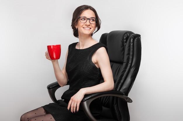 Картина красивая женщина в черном платье, сидя в кресле с кофе в руках Premium Фотографии