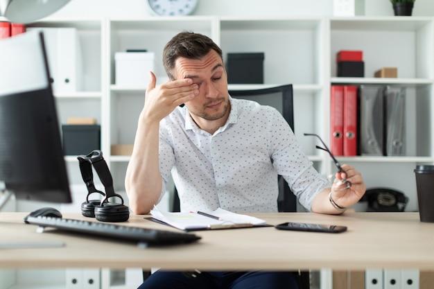 Молодой человек сидит за столом в кабинете, снял очки и потер глаза. Premium Фотографии
